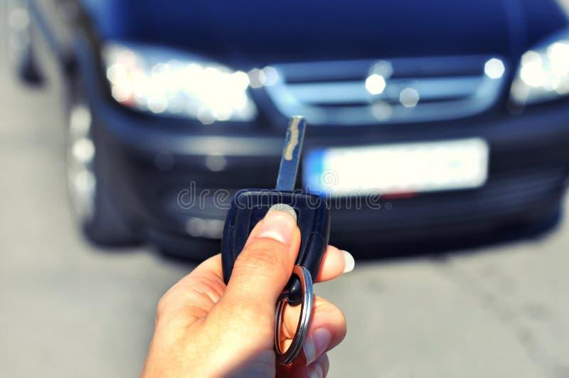 Mano que sostiene el botón en el coche remoto En el foco selectivo de la mujer la mano presiona en los sistemas de alarma para co foto de archivo