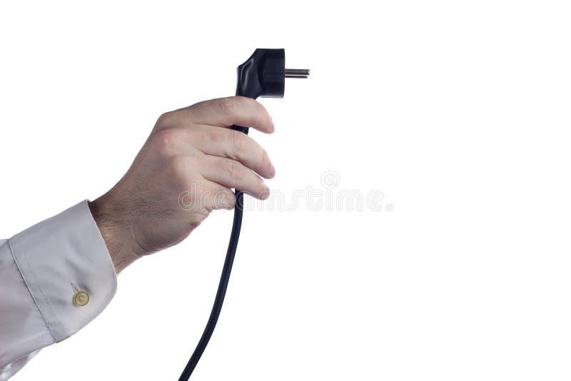 Mano que sostiene el cable eléctrico con el enchufe aislado en el fondo blanco foto de archivo libre de regalías