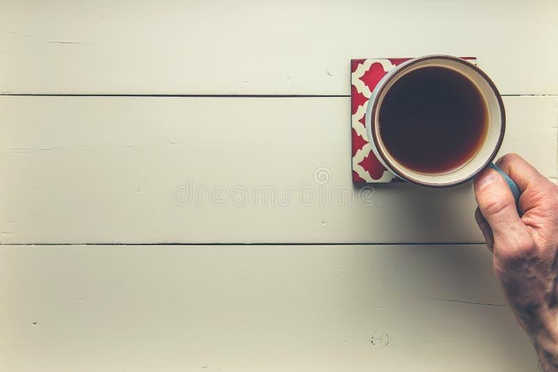 Mano que sostiene el café en la madera foto de archivo