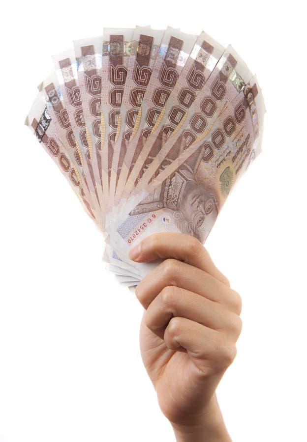 Mano que sostiene el dinero tailandés. imagenes de archivo