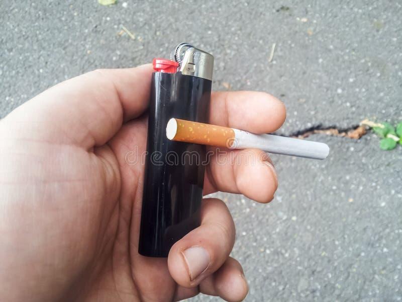 Mano que sostiene el encendedor y el cigarrillo foto de archivo libre de regalías