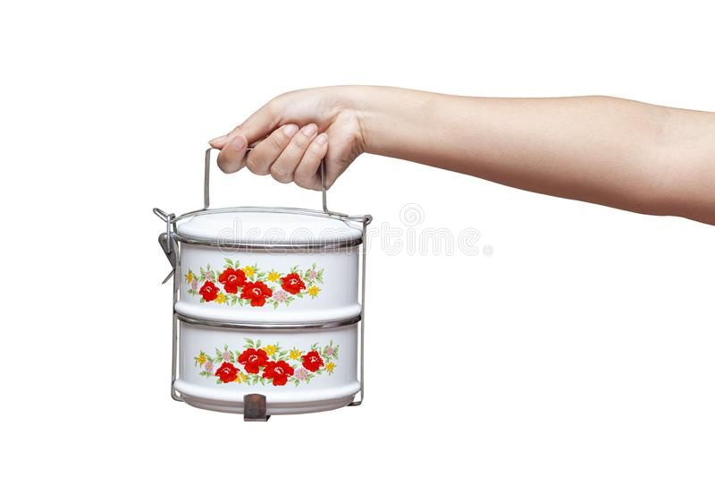 Mano que sostiene el envase del portador de la comida o de comida del tiffin imagen de archivo