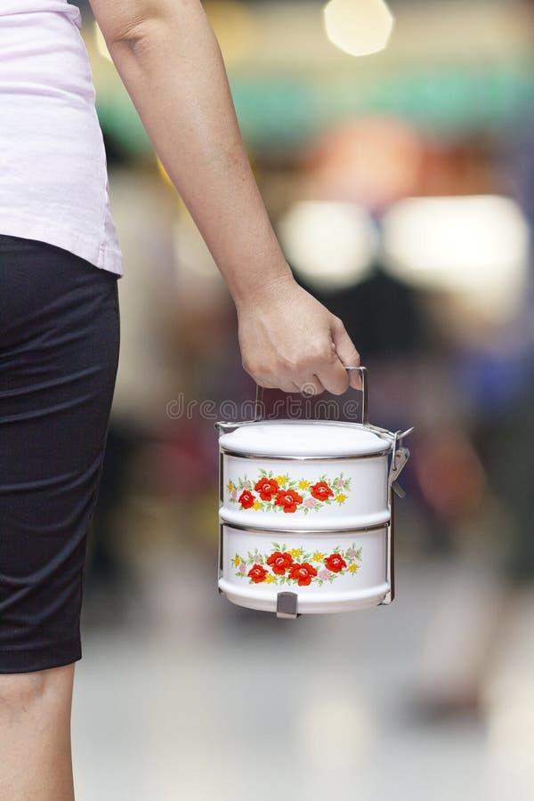 Mano que sostiene el envase del portador de la comida o de comida del tiffin fotos de archivo
