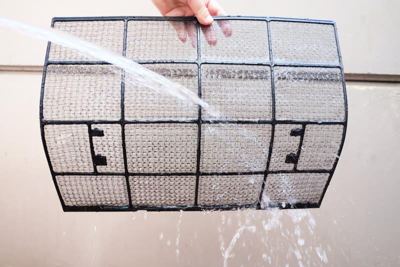Mano que sostiene el filtro sucio del aire acondicionado a la limpieza por el agua del espray fotos de archivo