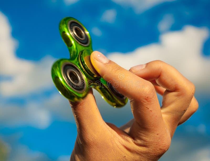Mano que sostiene el juguete verde del hilandero de la persona agitada fotos de archivo libres de regalías