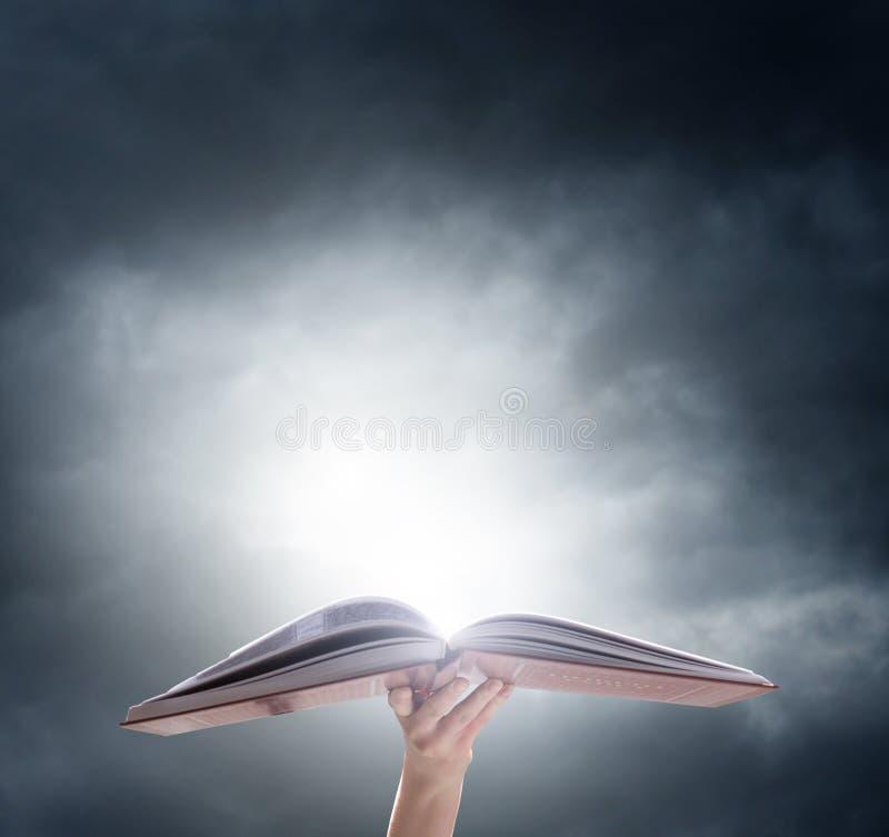 Mano que sostiene el libro mágico encendido abierto imagen de archivo libre de regalías