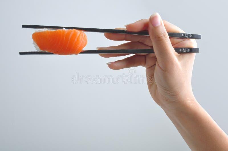 Mano que sostiene el palillo del sushi imagenes de archivo