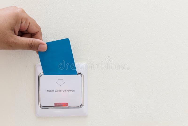 Mano que sostiene el parte movible azul de la llave electrónica del hotel al interruptor eléctrico fotos de archivo libres de regalías