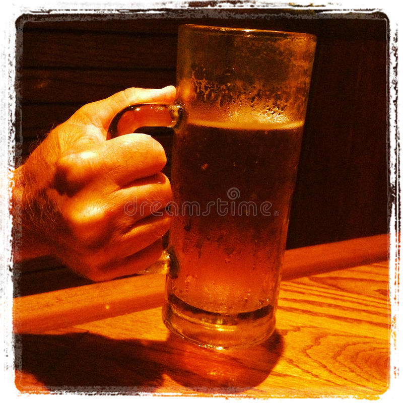 Mano que sostiene el primer de la cerveza foto de archivo