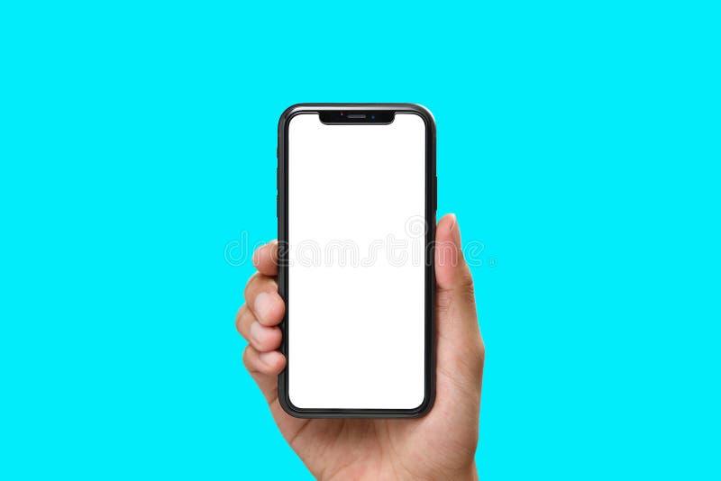 Mano que sostiene el smartphone negro con la pantalla en blanco fotografía de archivo