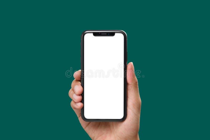 Mano que sostiene el smartphone negro con la pantalla en blanco imagen de archivo