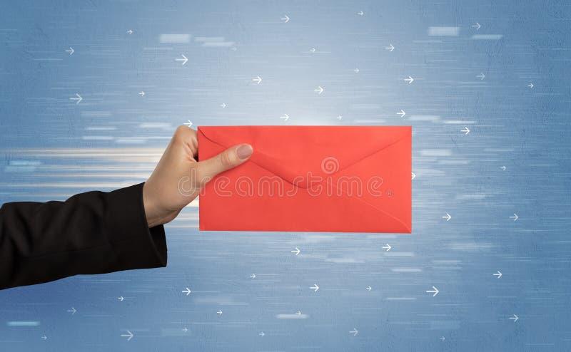 Mano que sostiene el sobre con las flechas alrededor fotos de archivo