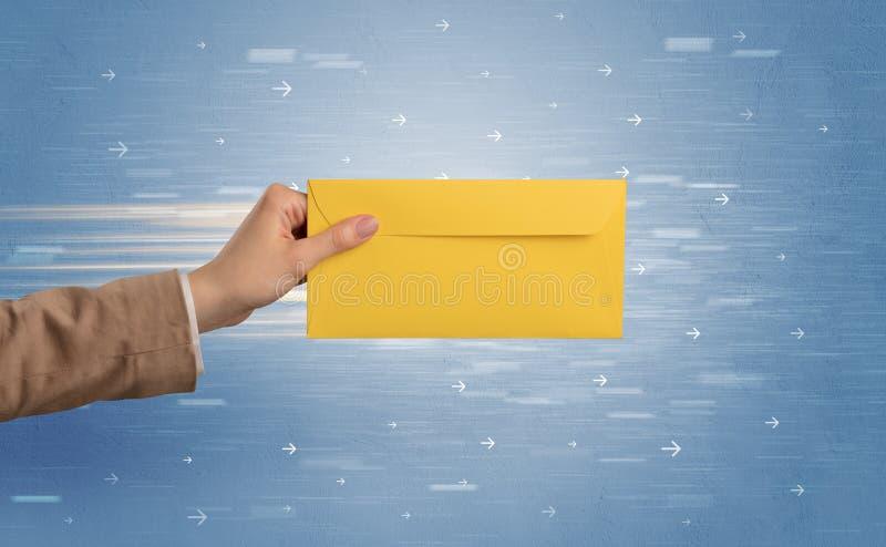 Mano que sostiene el sobre con las flechas alrededor foto de archivo libre de regalías