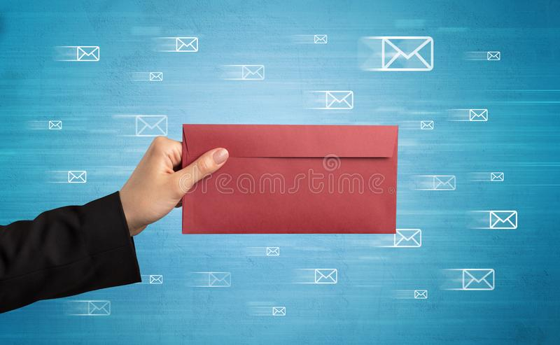 Mano que sostiene el sobre con símbolos del mensaje alrededor fotos de archivo