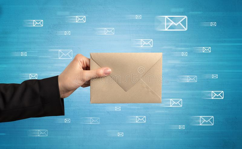 Mano que sostiene el sobre con símbolos del mensaje alrededor fotografía de archivo libre de regalías