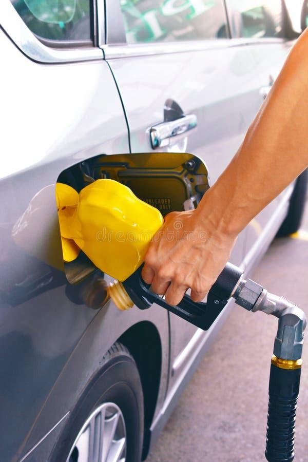 Mano que sostiene el surtidor de gasolina para añadir el gas imagen de archivo libre de regalías