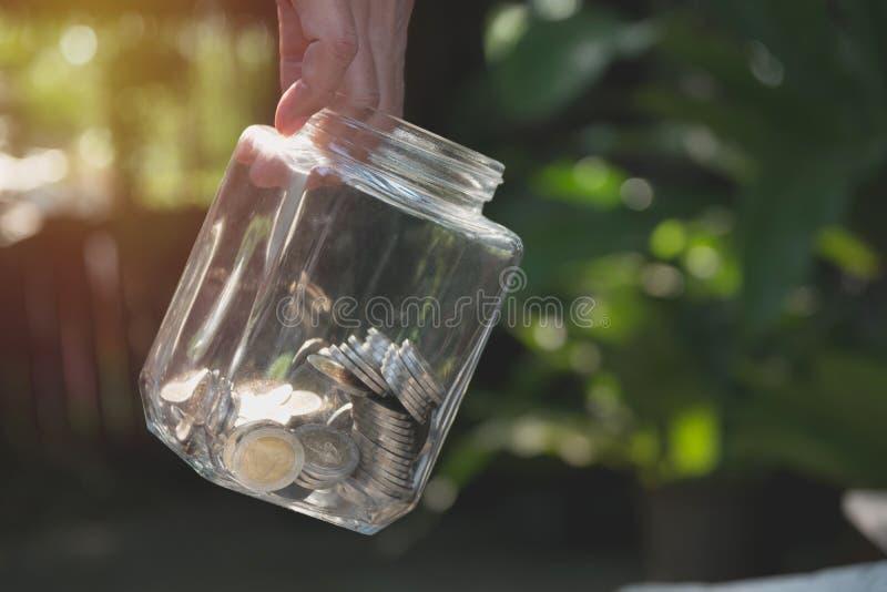 Mano que sostiene el tarro con las monedas Negocio y ahorro de las finanzas del concepto imagenes de archivo