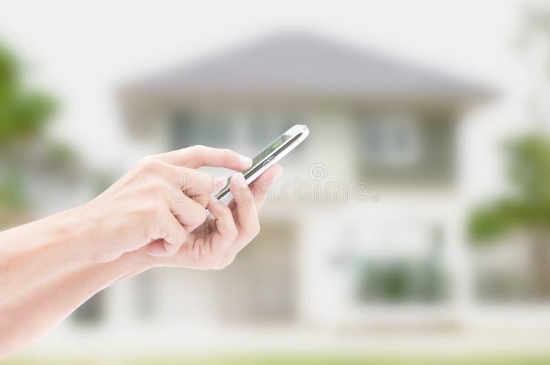 Mano que sostiene el teléfono elegante en fondo de la casa fotografía de archivo