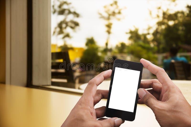 Mano que sostiene el teléfono elegante en sala de estar borrosa imágenes de archivo libres de regalías