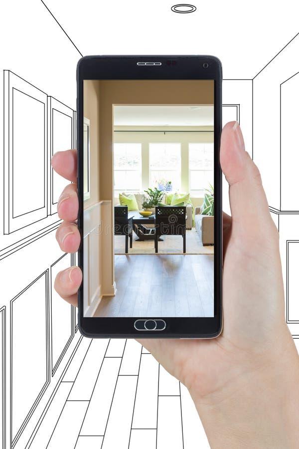 Mano que sostiene el teléfono elegante que exhibe la foto del vestíbulo Drawi de la casa foto de archivo libre de regalías