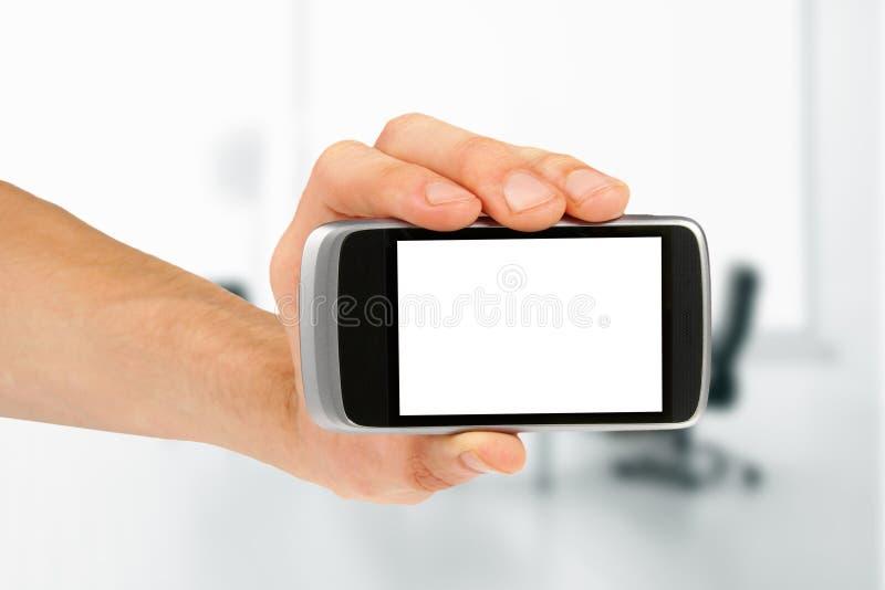 Mano que sostiene el teléfono elegante móvil en blanco imágenes de archivo libres de regalías
