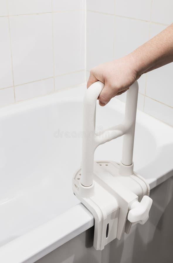 Mano que sostiene la barandilla en el cuarto de baño imagenes de archivo