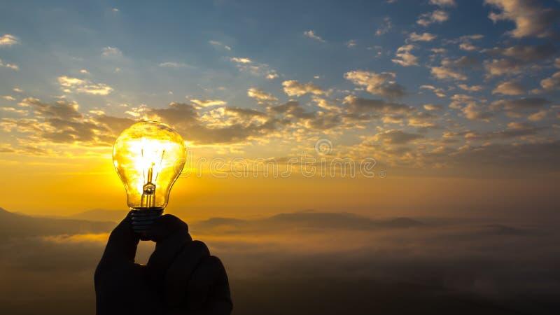Mano que sostiene la bombilla durante salida del sol imagen de archivo libre de regalías