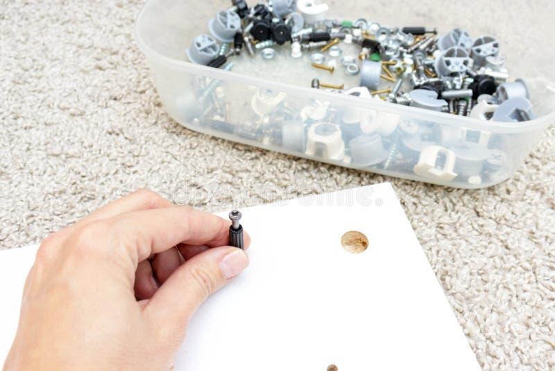 Mano que sostiene la colocación, la fijación o la sujeción para los muebles de junta del montaje hechos de conglomerado imágenes de archivo libres de regalías
