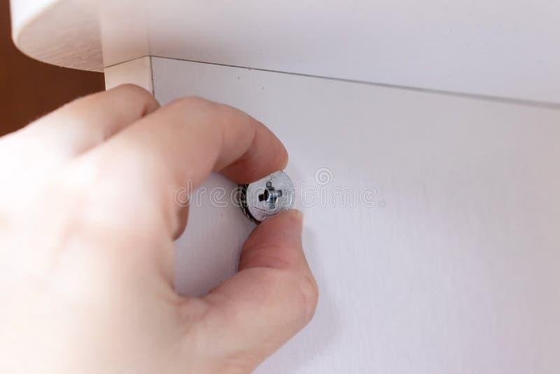 Mano que sostiene la colocaci?n, la fijaci?n o la sujeci?n para los muebles de junta del montaje hechos de conglomerado fotografía de archivo