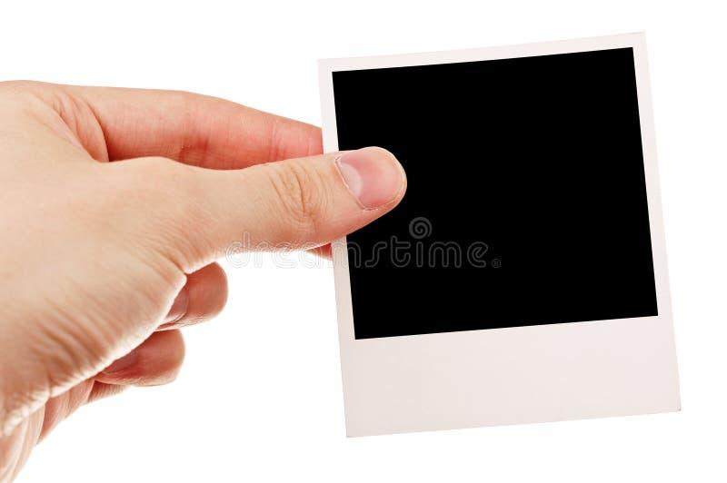 Mano que sostiene la foto en blanco fotos de archivo