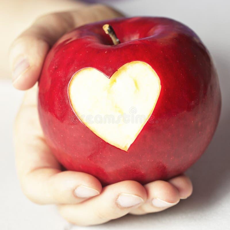Mano que sostiene la manzana roja con el corazón imagen de archivo