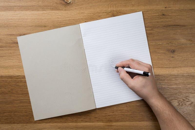 Mano que sostiene la maqueta de papel en blanco blanca de la hoja en fondo de madera fotografía de archivo libre de regalías