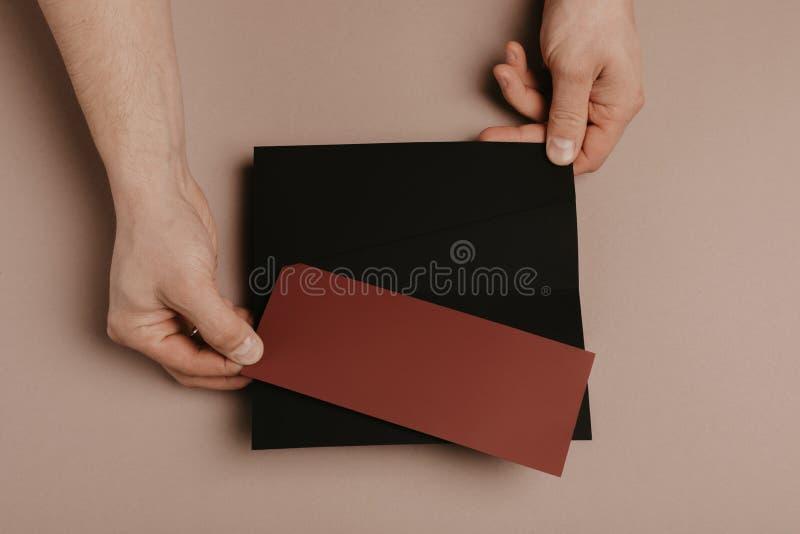 Mano que sostiene la maqueta en blanco del sobre y de la letra fotografía de archivo
