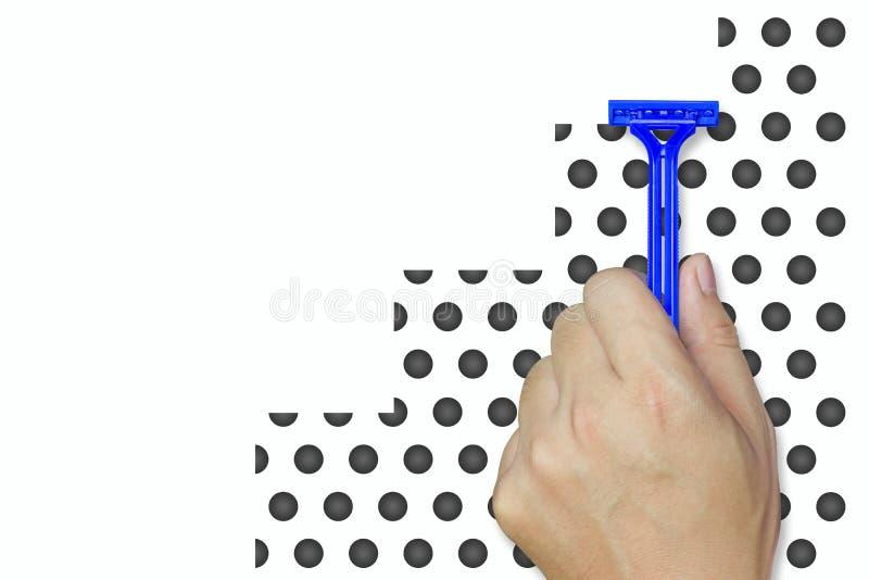 Mano que sostiene la maquinilla de afeitar azul en el simulador de la barba fotografía de archivo libre de regalías
