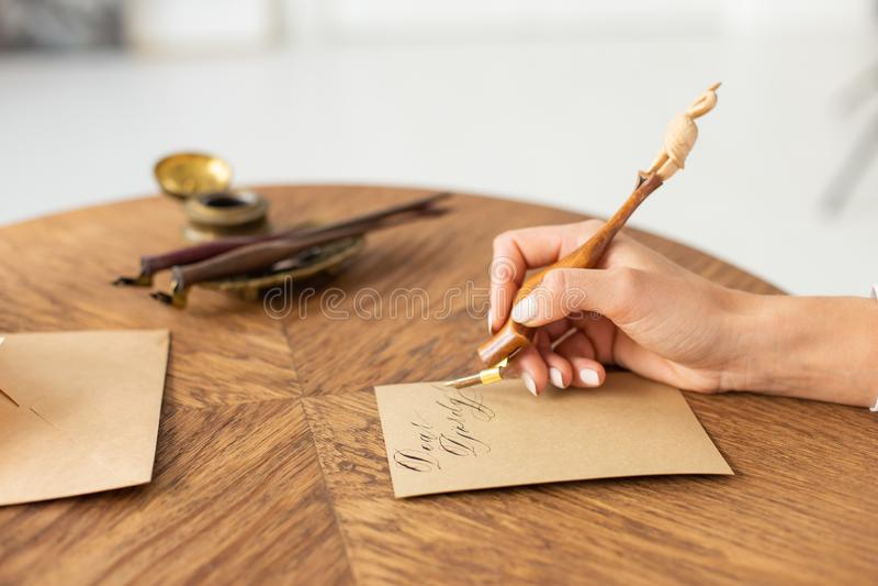 Mano que sostiene la pluma de la tinta El concepto de narración La muchacha escribe una letra en la tabla Foco suave Primer fotografía de archivo libre de regalías