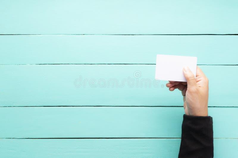 Mano que sostiene la tarjeta de visita en blanco imagenes de archivo