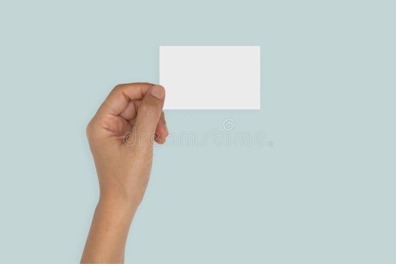 Mano que sostiene la tarjeta en blanco aislada en azul imagen de archivo