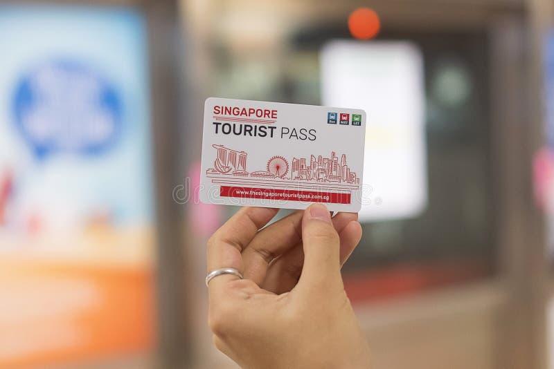 Mano que sostiene la tarjeta turística del paso de Singapur en el ferrocarril del MRT; Singapur, el 9 de mayo de 2019 fotos de archivo libres de regalías