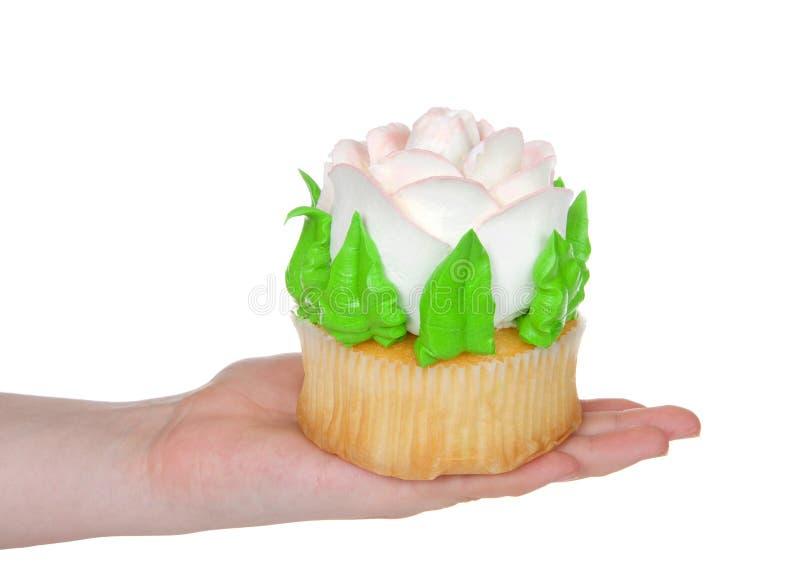 Mano que sostiene la torta color de rosa helada grande de la taza aislada en blanco fotografía de archivo