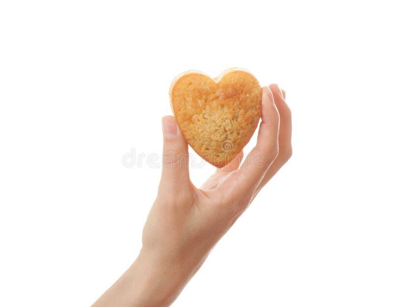 Mano que sostiene la torta del heartshape foto de archivo libre de regalías