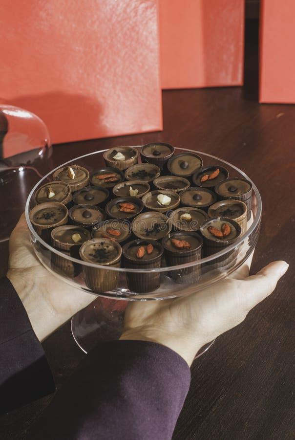 Mano que sostiene los caramelos del chocolate imagen de archivo