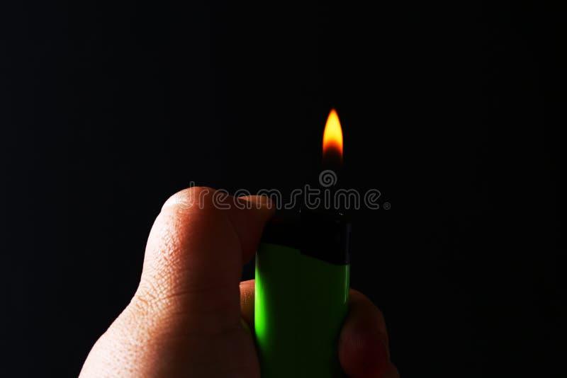 Mano que sostiene los encendedores de gas ardientes en fondo negro oscuro Dispositivo portátil usado para crear una llama imagen de archivo