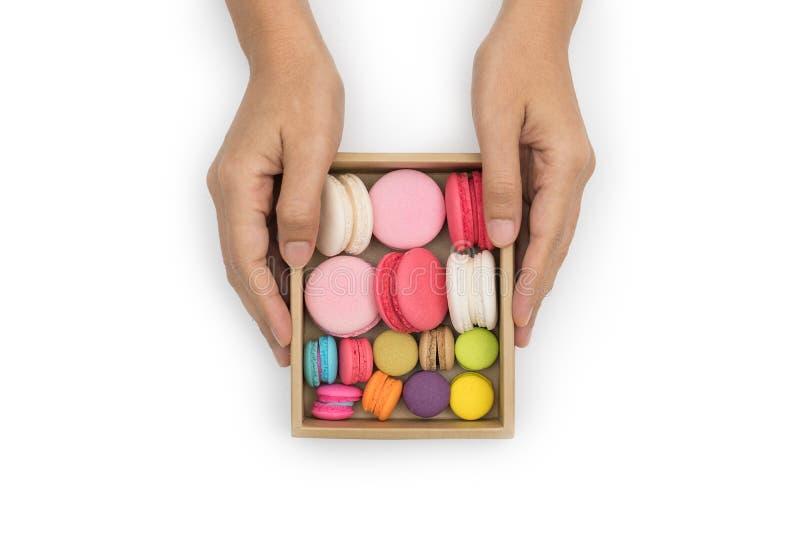 Mano que sostiene los macarrones coloridos, dulce y sabroso para cocinar y foto de archivo libre de regalías