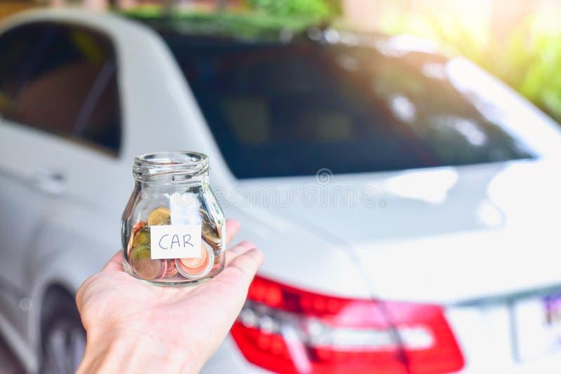 Mano que sostiene monedas en el tarro de cristal con la etiqueta del coche delante de un coche de lujo imágenes de archivo libres de regalías