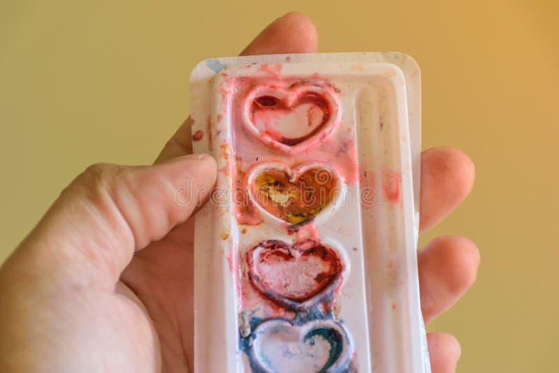 mano que sostiene muchos forma del corazón del color imágenes de archivo libres de regalías