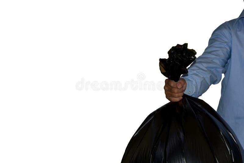 Mano que sostiene un bolso de basura negro imagen de archivo