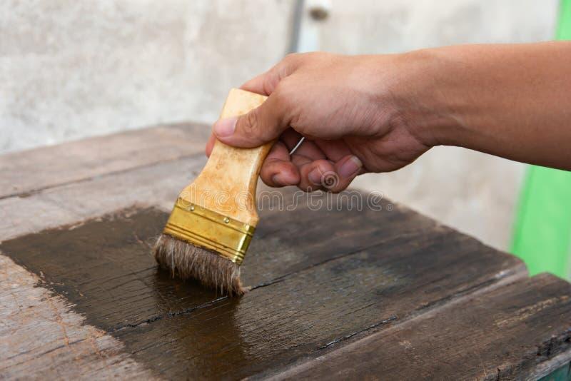Mano que sostiene un cepillo que pinta la superficie de madera de los tableros de la madera con la mancha de madera fotos de archivo libres de regalías