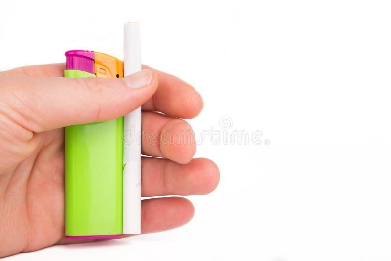 Mano que sostiene un encendedor y un cigarrillo imagen de archivo libre de regalías