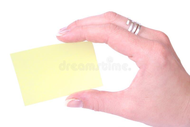Mano que sostiene un notecard en blanco amarillo fotografía de archivo