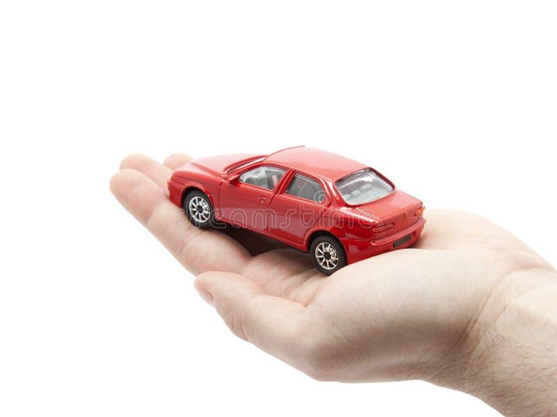Mano que sostiene un pequeño coche rojo foto de archivo